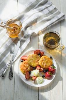 Сырники с медовым чаем и ягодами на деревянном столе