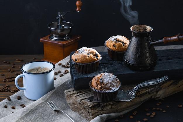 ホットコーヒーと木製の板、素朴なスタイルのカップケーキ