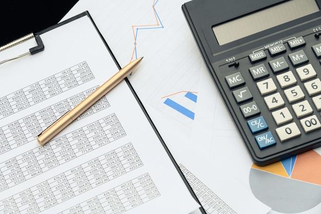 Деловые финансовые документы, офисный калькулятор и ручка на столе. числа и графики