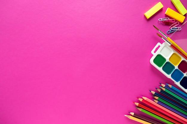 ピンクの背景に学用品のフラットが横たわっていた。教育のコンセプトです。