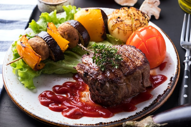 ジューシーなミディアムビーフステーキとレッドソースとグリル野菜のプレート。閉じる
