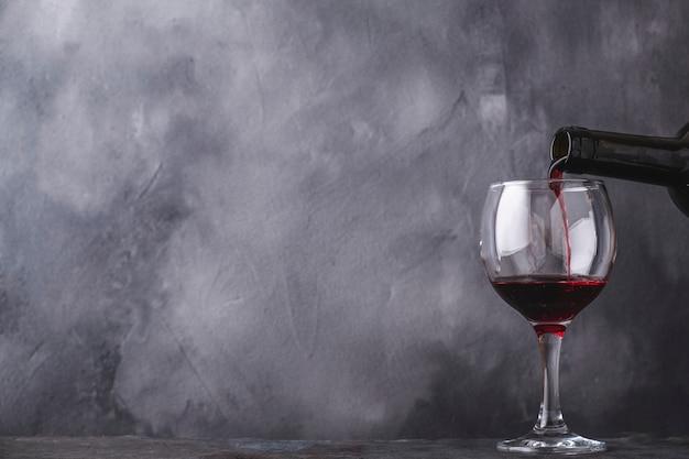 Лить красное вино в стакан из бутылки. пространство для текста