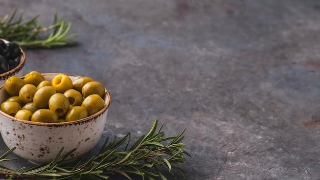 Оливки в миске с розмарином.