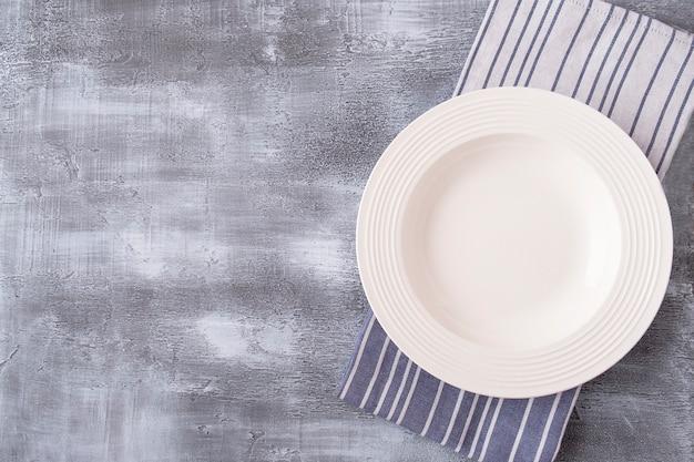 Пустая тарелка на серой поверхности. вид сверху.