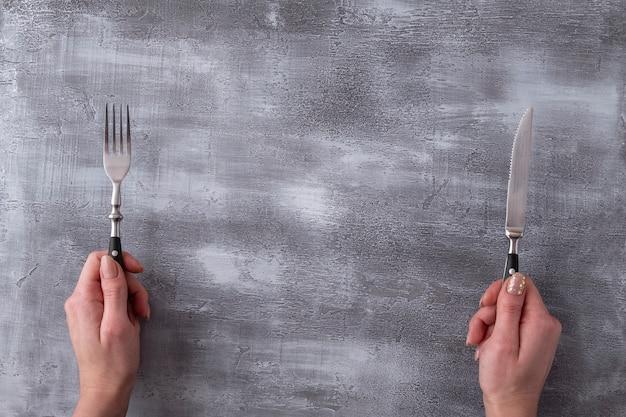 灰色の表面にフォークとナイフを保持している手。 。上面図