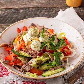 木製の素朴な表面に肉サラダ野菜とウズラの卵