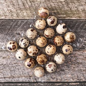 木製の表面のプラスチックトレイにウズラの卵。上面図