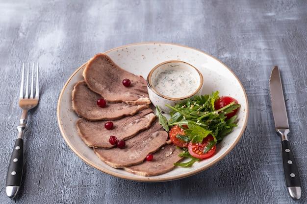 おいしいスライスされた牛タンは、フォークとナイフを提供しています。