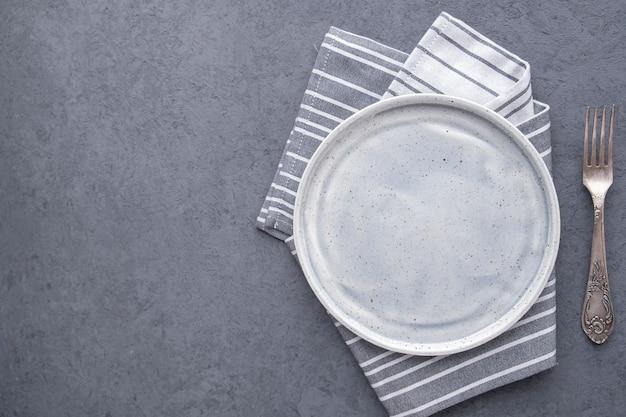 Пустая тарелка вилка на серой поверхности. вид сверху. ,