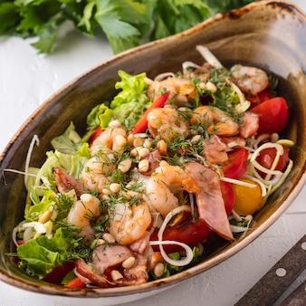 Салат с креветками, жареным беконом, овощами и кедровыми орешками.