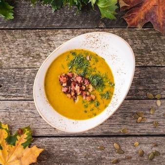 Вкусный тыквенный крем-суп с жареным беконом и луком. вид сверху