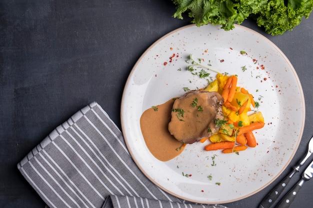 Запеченная свинина под соусом из запеченных овощей. вид сверху.