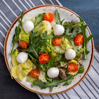新鮮なサラダトマト、ルッコラ、レタス、モッツァレラチーズのプレート。上面図。閉じる