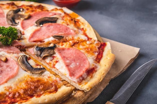 Вкусная пицца с грибами и ветчиной. вкусная домашняя пицца