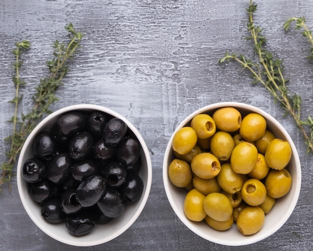 Черные и зеленые оливки в миску. вид сверху.