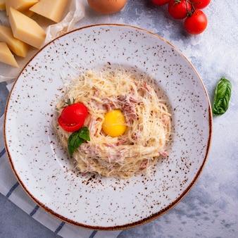 Классическая итальянская паста спагетти по-бальоново с беконом, яйцом, сыром пармезан и сливочным соусом. вид сверху.