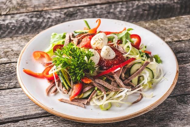 牛タン、野菜、木製の素朴な背景にウズラの卵のおいしいサラダ