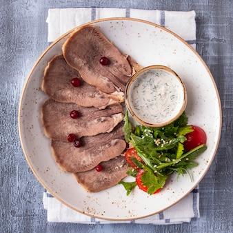 スライスした牛タンクランベリー、サラダ、ソース。冷たい牛肉スナック。上面図。閉じる
