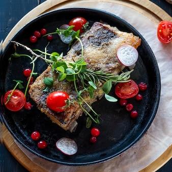 Вкусные запеченные свиные ребрышки подают свежую зелень и помидоры на сковороде. вид сверху