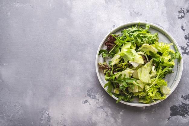 プレート上の新鮮な野菜のミックス。新鮮な夏のグリーンサラダ。上面図。