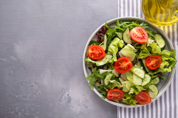 皿にサラダキュウリとフレッシュトマトの新鮮なミックス。健康とダイエット食品。上面図。