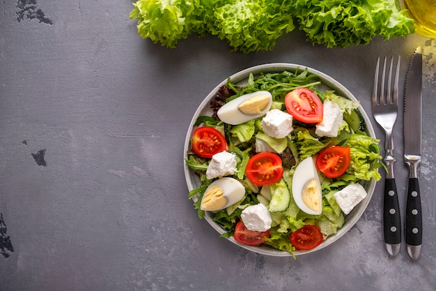 野菜サラダの卵、チーズ、プレート上のミックスグリーン。健康食品。上面図。