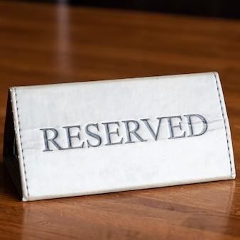 レストランの木製テーブルの予約サイン。テーブル設定予約記号