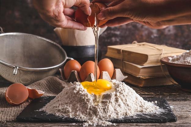 女性の手は卵を小麦粉に砕きます。