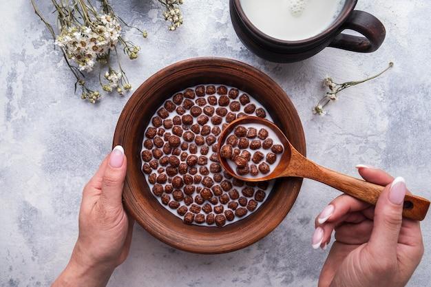 スプーンチョコレートシリアルボールを持っている手。健康的な朝食とダイエットのコンセプト。上面図。