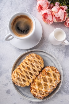 一杯のコーヒーと牛乳の皿に新鮮なリンゴのペストリー。健康的な朝食のコンセプト。上面図。