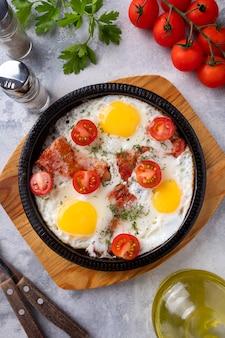 Жареные яйца, бекон и овощи на сковороде. время завтрака. вид сверху.