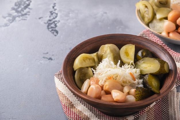 Квашеная капуста, огурцы, помидоры и чеснок на тарелке.