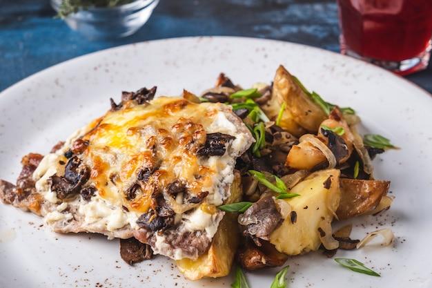 Крупный план испеченного мяса под грибами сыра.