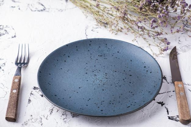 Пустая круглая тарелка с вилкой и ножом