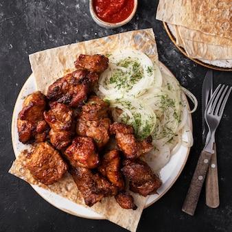 皿に焼きサシリク肉。バーベキュー豚肉。上面図