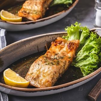 Филе лосося на гриле с лимоном и листьями салата на тарелке. крупный план