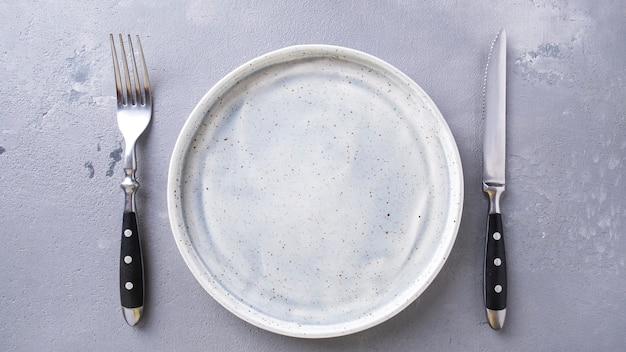 Пустая серая тарелка вилка и нож. вид сверху.