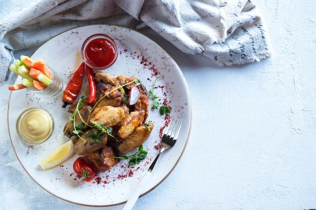 Вкусные куриные крылышки подаются с острым перцем, сельдереем и морковными палочками. вид сверху.