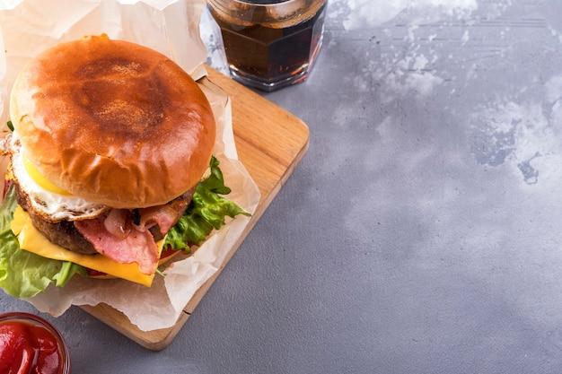 Сочный жареный по-домашнему гамбургер из говядины, бекона, яиц, помидоров, сыра и салата. вид сверху
