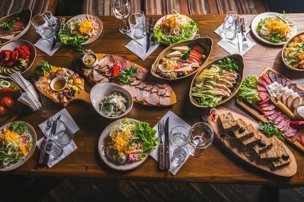 Закуски столовые. разнообразие блюд. семейный праздничный стол. тонированное фото. вид сверху