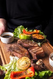 ウェイターは、牛タンのグリルと野菜で木の板を保持します