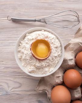 ベーキングのための原料:テーブルの上の小麦粉、卵および卵黄。