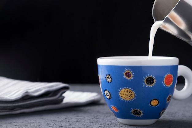 Свежее молоко наливают в чашку кофе.