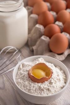 パンの材料-小麦粉、卵、牛乳、テーブルの上の卵黄。甘いペストリーベーキングコンセプト。閉じる