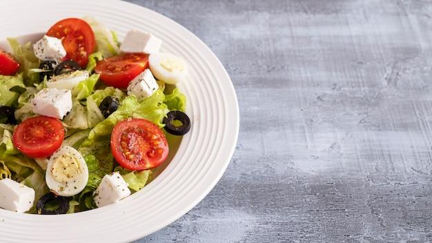 トマト、ウズラの卵、レタス、チーズ、プレート上のブラックオリーブ。健康とダイエット食品のコンセプト。コピースペース