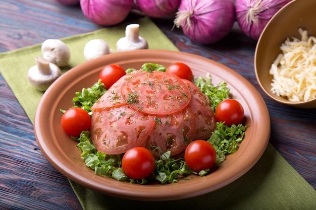 Мясо с помидорами, сыром и грибами на деревянном