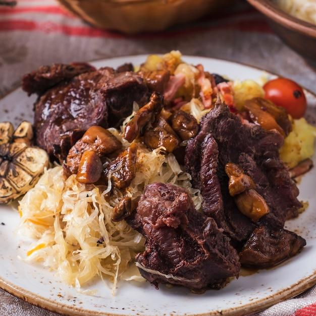 Говяжьи щечки с картофелем, квашеной капустой и грибами.