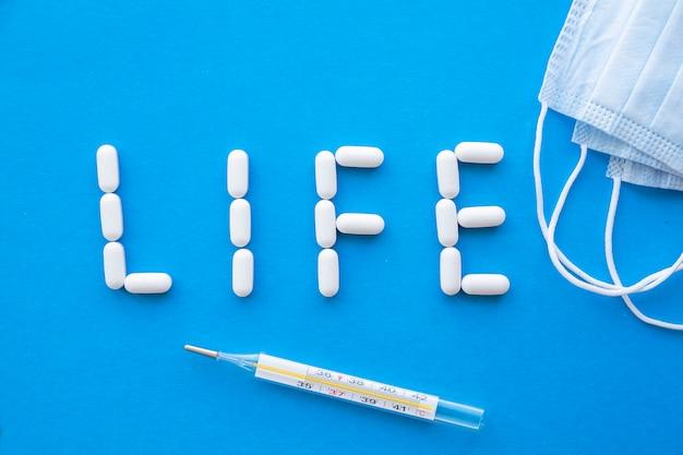 青の背景に薬で書かれた単語の生活。コロナウイルスの概念。上面図