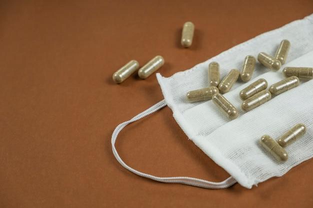 Медицинская маска и таблетки на темном фоне. пространство для текста