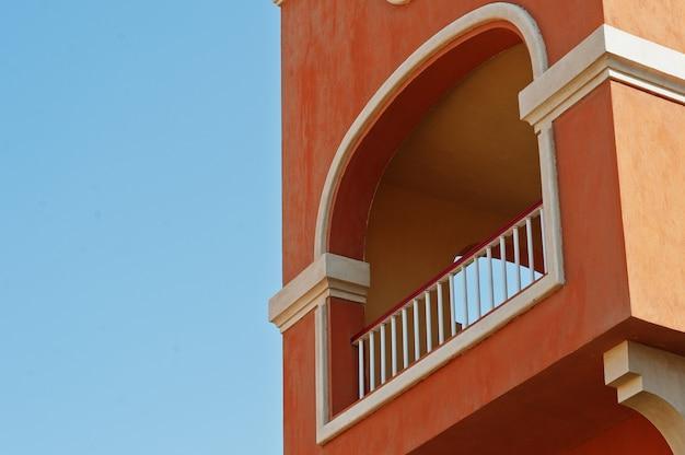 アラビアのオレンジ色の家の背景の青い空のバルコニーアーチ